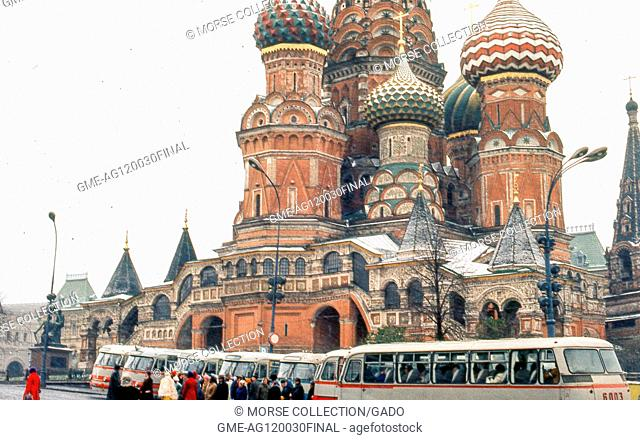View facing northeast of St Basil's Cathedral in Red Square, Moscow, Soviet Russia (USSR), November, 1973. Travelers congregate beside their tour buses idling...