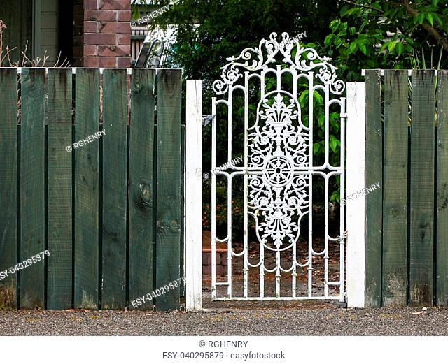 Metal white gate in a green wooden fence