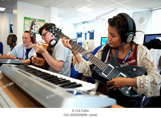 Small group of college students sitting in front of keyboards wearing headphones playing guitars