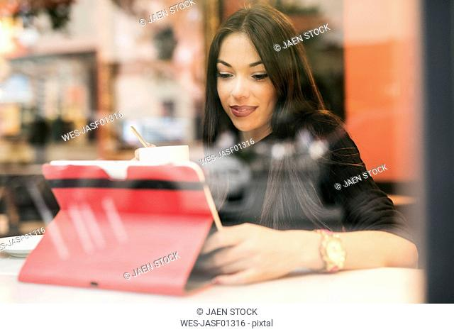 Young woman sitting behind windowpane of a coffee shop looking at tablet