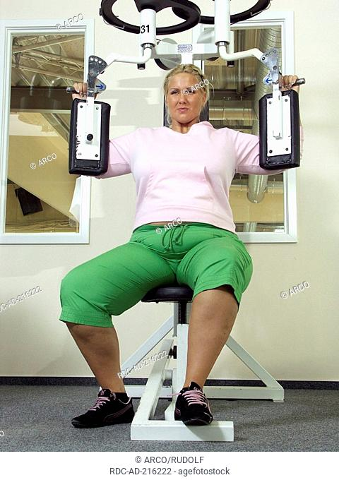 Corpulent woman in fitness studio, training, weight reduction, strain, exhausting