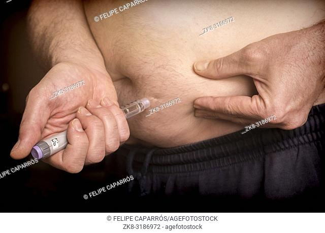 Man daily dose of insulin in the belly, conceptual image