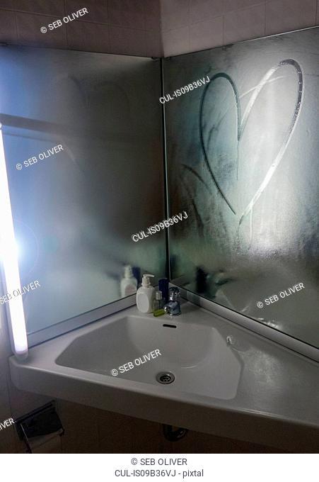 Heart drawn on steamy bathroom mirror