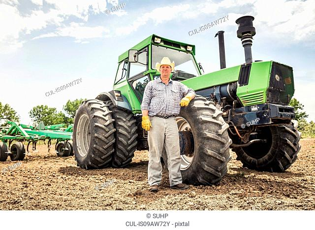 Portrait of male farmer leaning against tractor in ploughed field