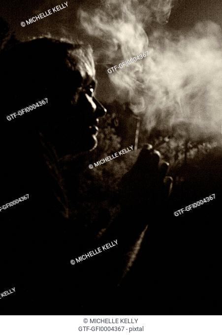 Profile of man smoking in the dark