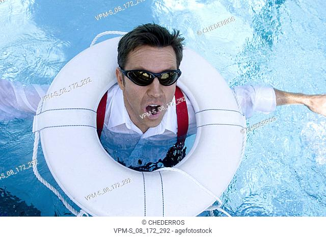 High angle view of a mid adult man with a life belt in a swimming pool