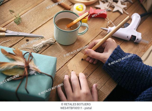 Woman writing on Christmas present tag, close-up