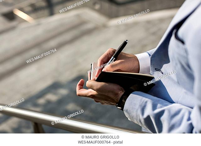Businessman writing in diary outdoors
