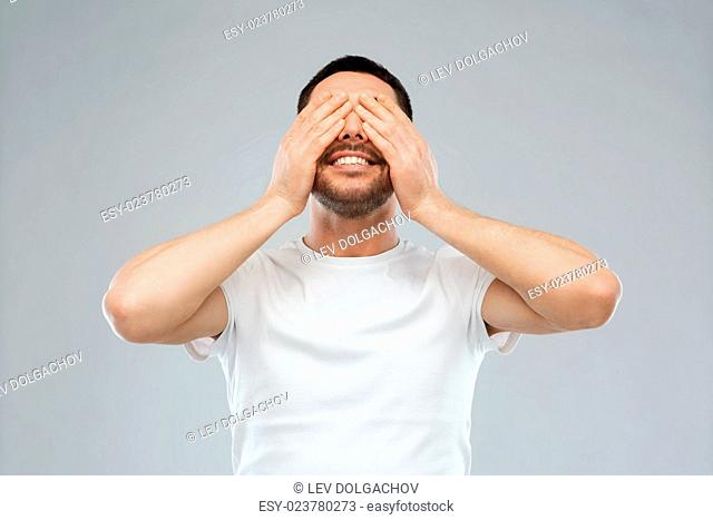 emotion, vision and people concept - smiling man closing his eyes with hands over gray background