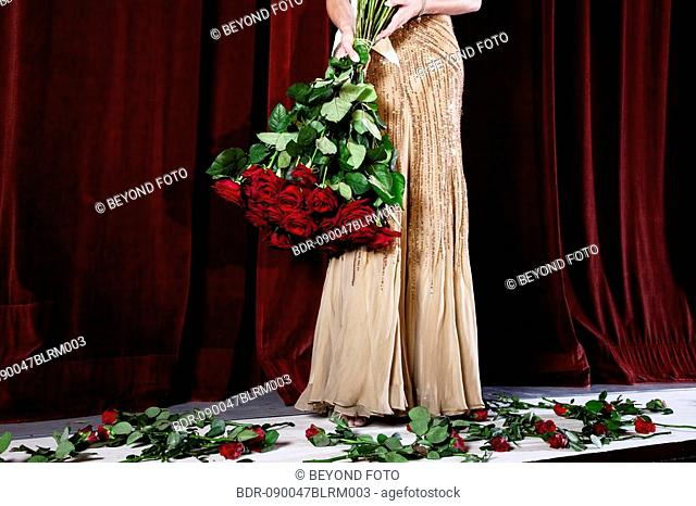 detail of winner of beauty contest on stage with bunch of red roses