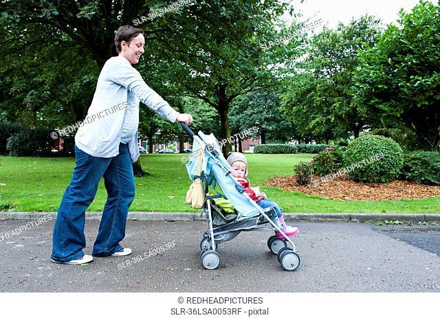 Mother pushing daughter in stroller