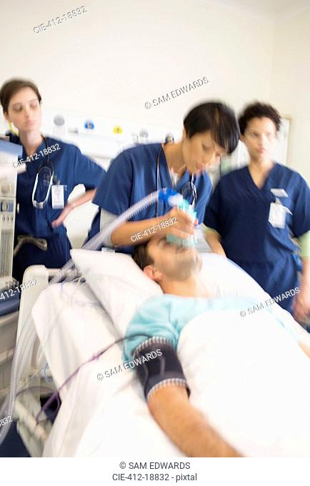 Team of doctors giving oxygen to patient in intensive care unit