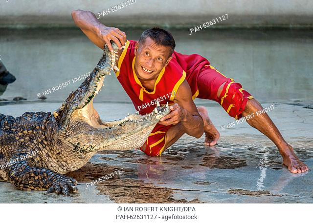 An artists reaches his head into the mouth of a crocodile during a performance at the crocodile farm in Samut Prakan,Thailand, 13 October 2015