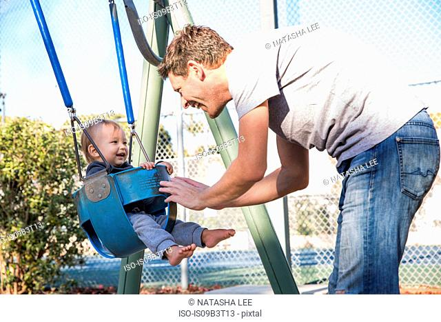 Father pushing young son on playground swing