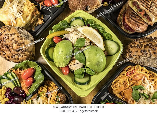 A buffet of fast food. Chicken and avocado salad, pasta, and foccacia