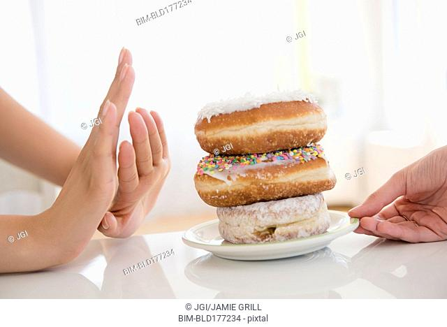 Woman refusing plate of donuts