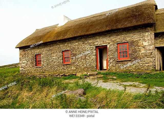 rural old irish stone cottage with red windows