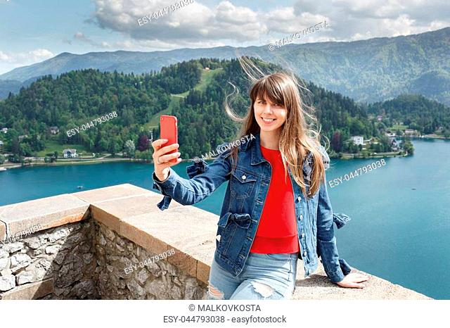 Girl taking selfie from castle top of the mountain with valley view and lake on the background. Travel Slovenia, Europe. Bled Lake with Island