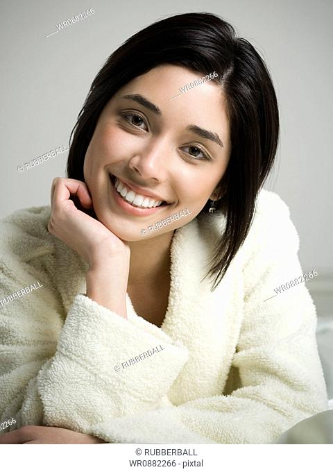 Portrait of a young woman smiling with her hand on her chin