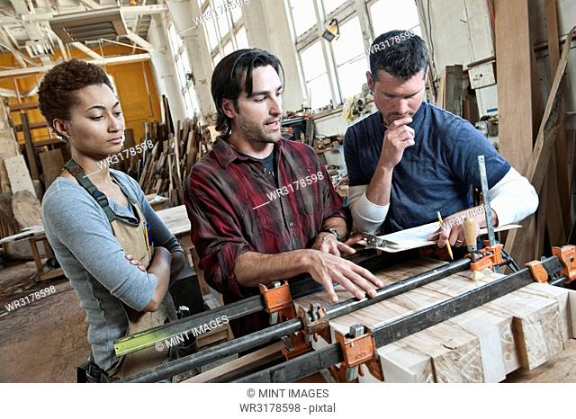 Team of multi-racial workers discussing an issue related to glueing a part together in a woodworking factory