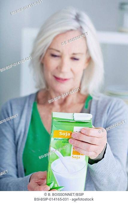 Senior woman reading the composition of soy milk