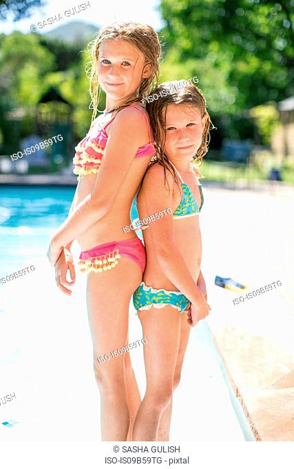 Portrait of two sisters back to back in bikinis by outdoor swimming pool