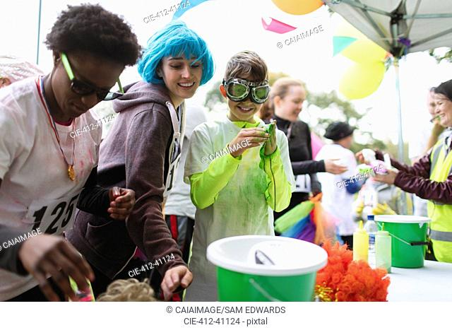 Runners with wig and holi powder at charity run tent