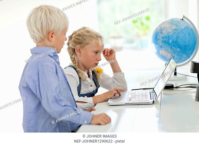 Girl and boy working on laptop
