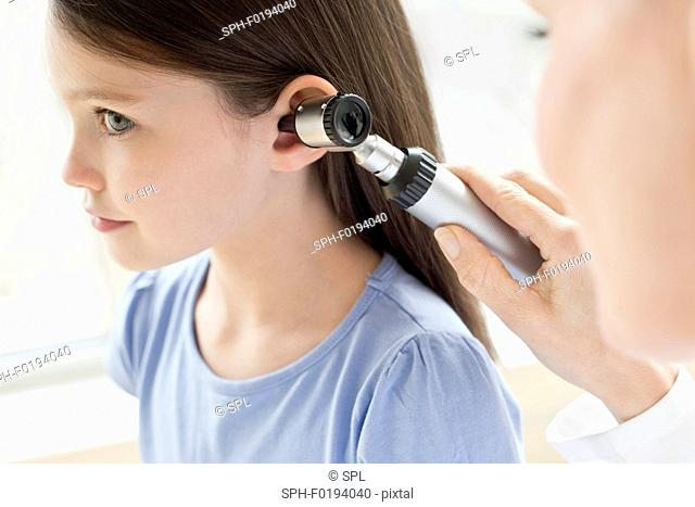 Female doctor examining girl's ear