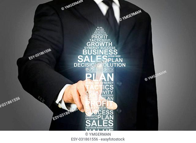Businessman clicking on an upward arrow formed by business related words
