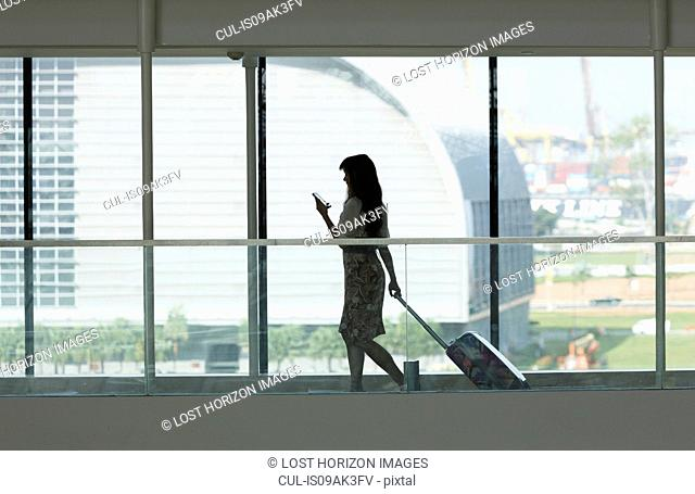 Young woman using smartphone and pulling suitcase in airport