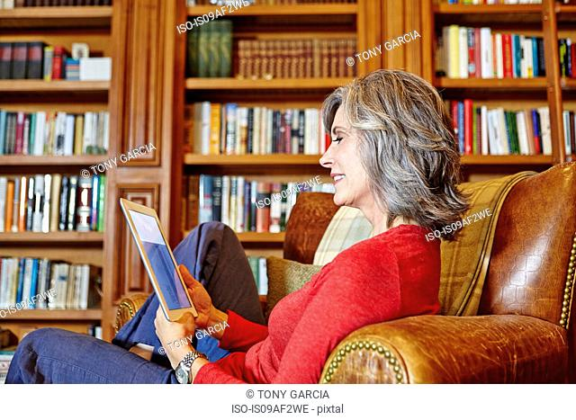 Mature woman sitting in home study using digital tablet