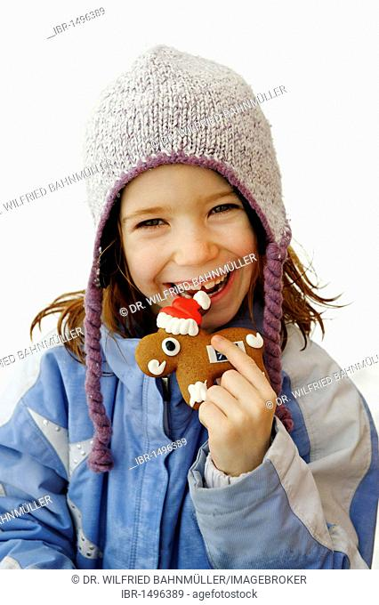 Child with gingerbread, shaped like moose