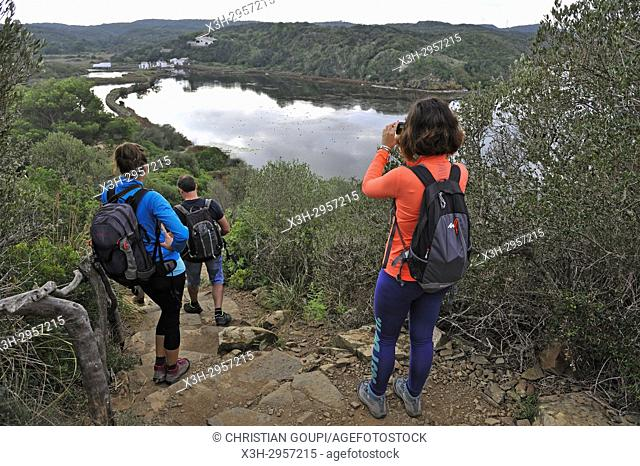 ramblers on a path overhanging the lagoon of s'Albufera des Grau Natural Park, Menorca, Balearic Islands, Spain, Europe