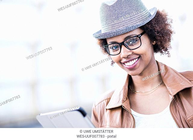 Portrait of smiling young woman wearing hat and glasses