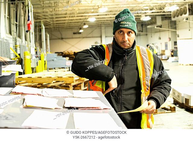 New York City, USA. Wholesale market stall employee crunching numbers after preparing orders for customers at the New Fulton Fish Market, Hunts Point, The Bronx