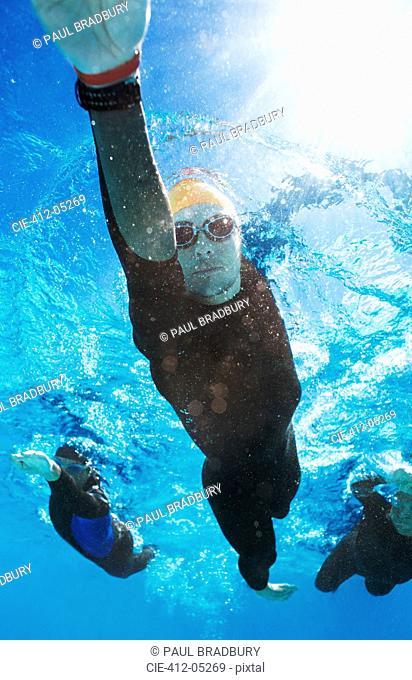 Triathletes in tri suits underwater