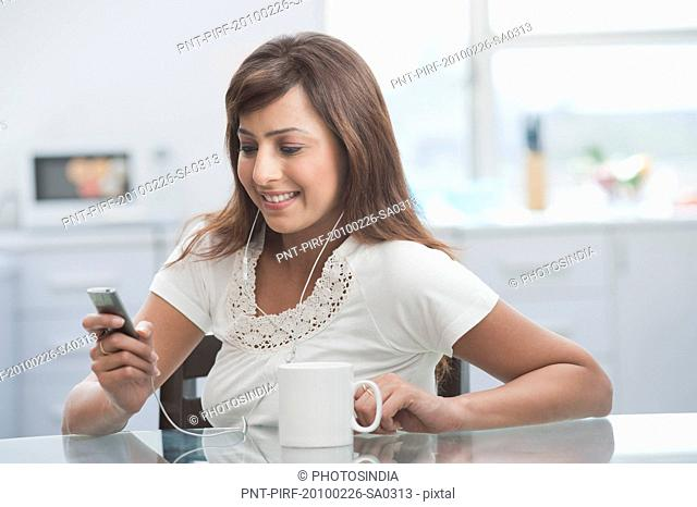 Woman listening to an MP3 player in the kitchen