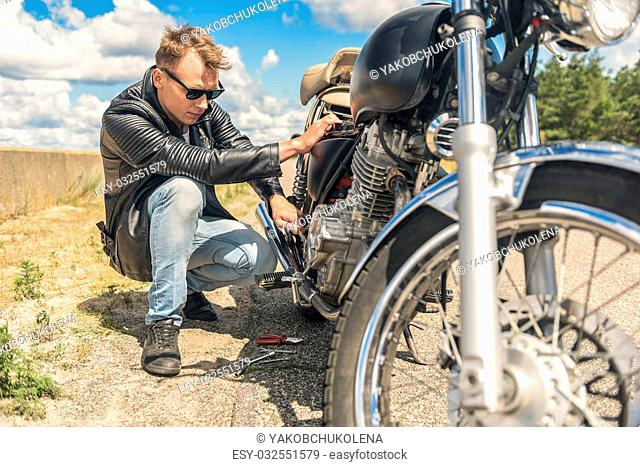 Taking care of my friend. Young man in sunglasses and leather jacket doing motorcycle maintenance on road