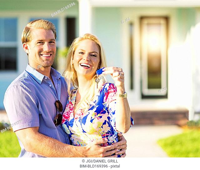 Caucasian couple holding keys outside new home