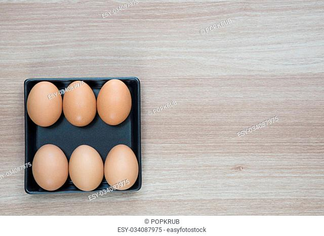 Six eggs in black square plate on wooden surface with space for text