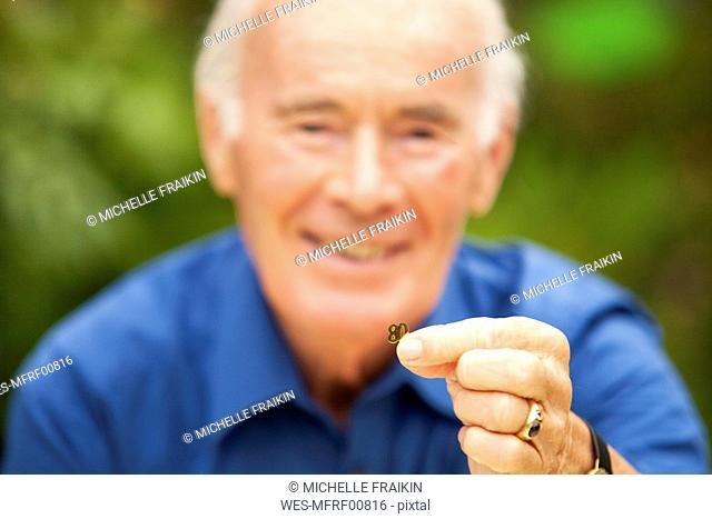 Senior man holding number 80