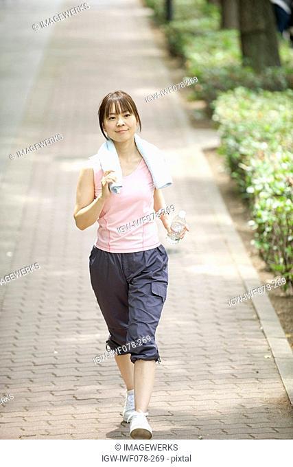 Japan, Osaka Prefecture, Woman walking on path, smiling
