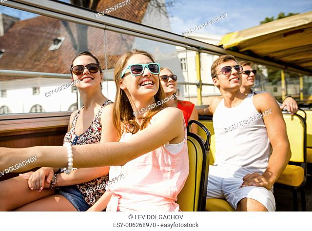 friendship, travel, vacation, summer and people concept - group of smiling friends traveling by tour bus