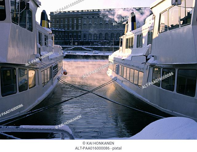 Sweden, Stockholm, view of building from between two docked yachts