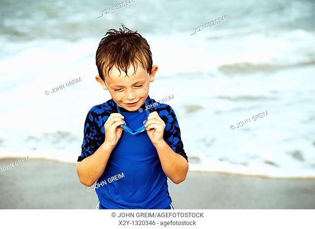 Young boy with goggles enjoys the ocean water