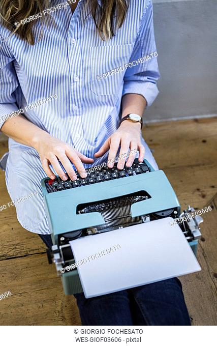 Close-up of woman sitting on the floor using typewriter
