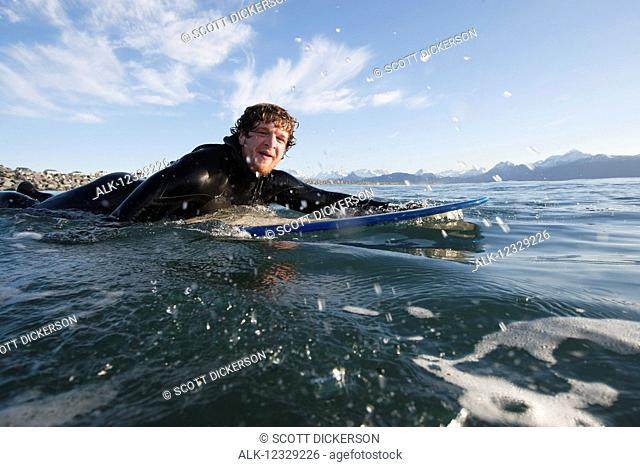 Surfer paddles out into the ocean, Southeast Alaska; Yakutat, Alaska, United States of America