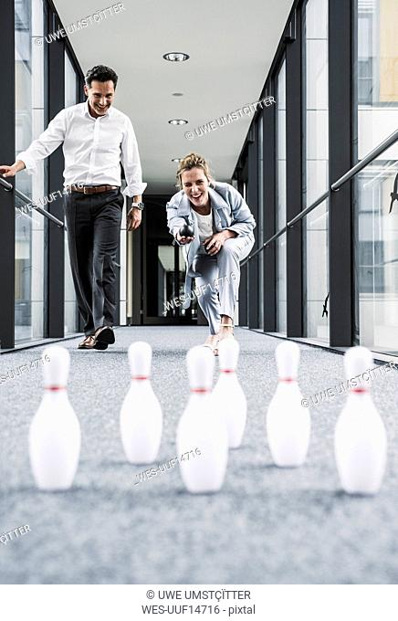 Happy businessman and businessman bowling in office passageway