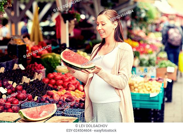sale, shopping, food, pregnancy and people concept - happy pregnant woman choosing watermelon at street market